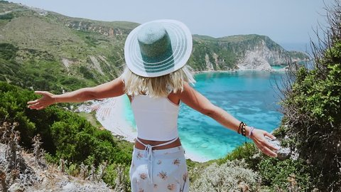Woman with sun hat spreading arms in front of beautiful seascape on Kefalonia island. Blonde female tourist standing on hill admiring dreaming panorama of blue bay, arms wide open, Greece.