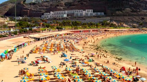 Aerial view of the famous Amadores beach and seafront with palm trees and people lying on the beach. Spanish resort. Gran Canaria, Canary islands, Spain