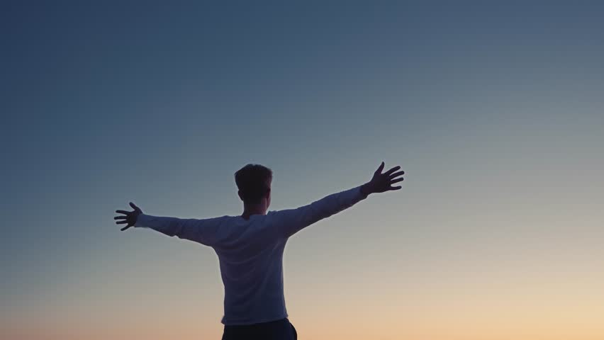 Conceptual video of the winner . A man raises his hands up, standing on a mountain top, above the clouds and blowing strong wind | Shutterstock HD Video #1020525874