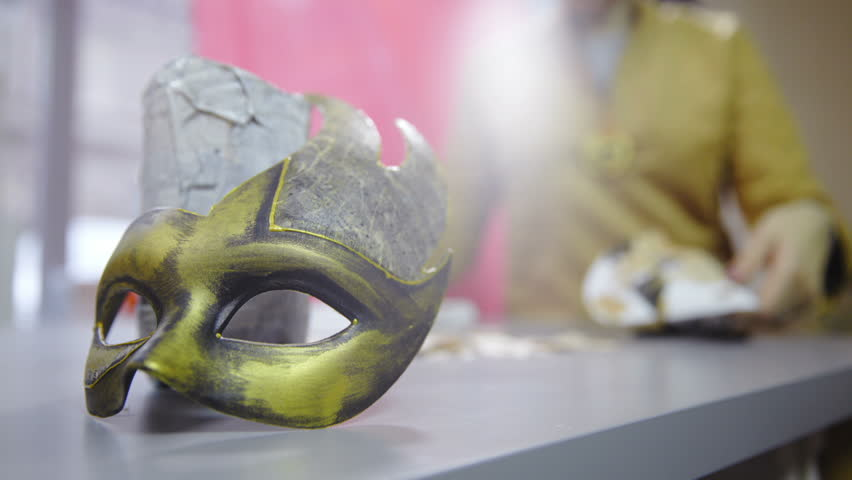 Sliding pass golden carnival mask to person creating new HD. Beautiful carnival mask lying on table while a person in background making new creative mask with glue and fragments of newspaper. | Shutterstock HD Video #1020542584