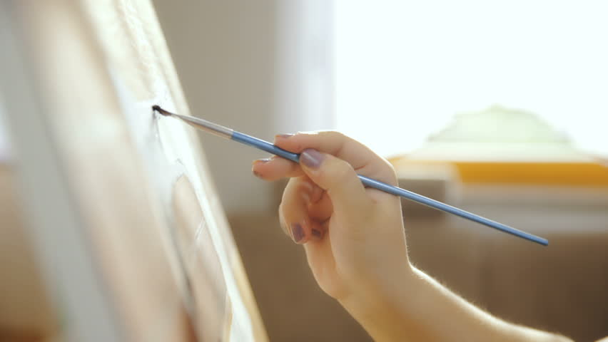 Dolly slide canvas from side while artist painting HD. Long shot close up on person hand in focus holding paint brush and painting on canvas. Window bright light in background shining. | Shutterstock HD Video #1020606544