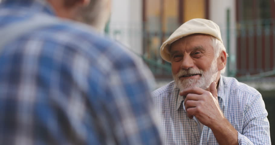 View over the shoulder on the Caucasian smiled old man in a cap talking cheerfully while playing with his best friend. Portrait. Rear. Outside. | Shutterstock HD Video #1020618784