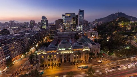 Day to night sunset timelapse hyperlapse of the historic national library of Santiago Chile in city downtown near Santa Lucia. Biblioteca Nacional de Chile. Skyscraper building in background.