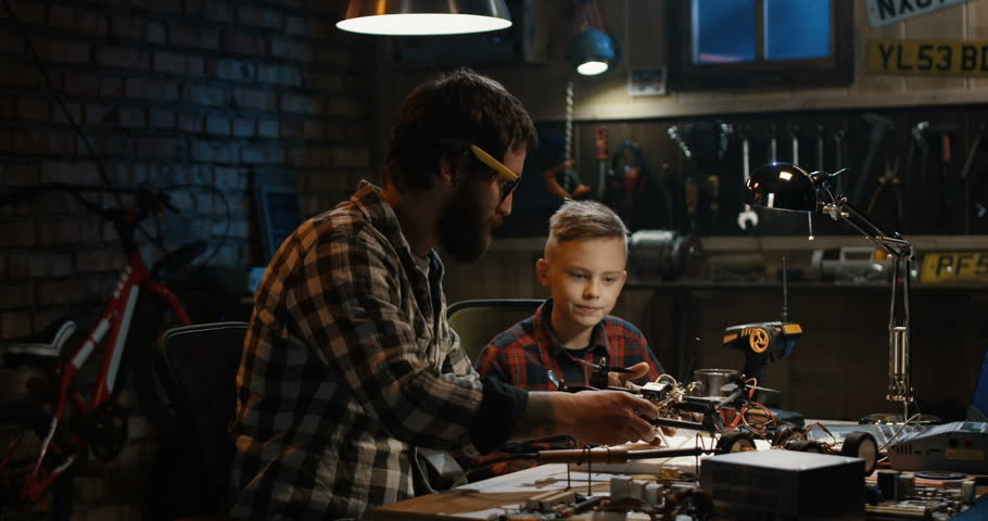 Medium shot of a father and son repairing a drone in a garage