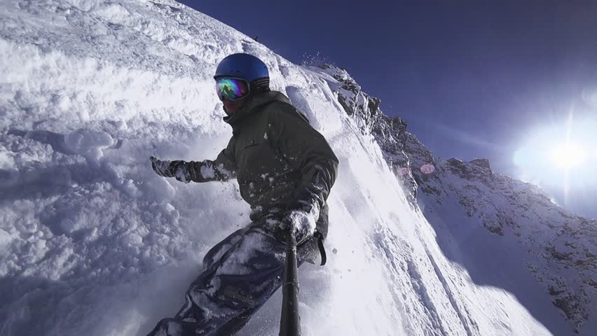 Person snowboarder snowboarding down slope closeup with gopro view white powder snow - winter extreme sports background