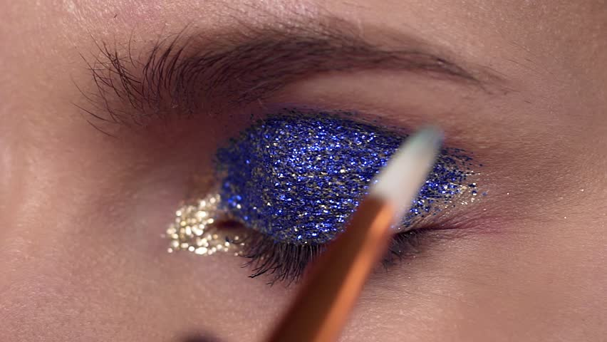 Glitter are applied to the woman's eyelid, making of the evening makeup, eyes makeup, makeup artist's work, close up makeup | Shutterstock HD Video #1020751144