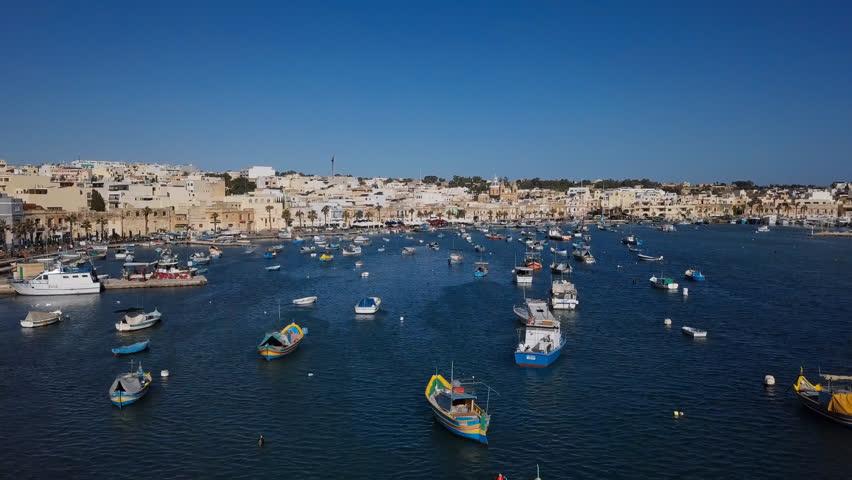 Flight over harbour with traditional fishing boats in fishing village Marsaxlokk, Malta | Shutterstock HD Video #1020788854