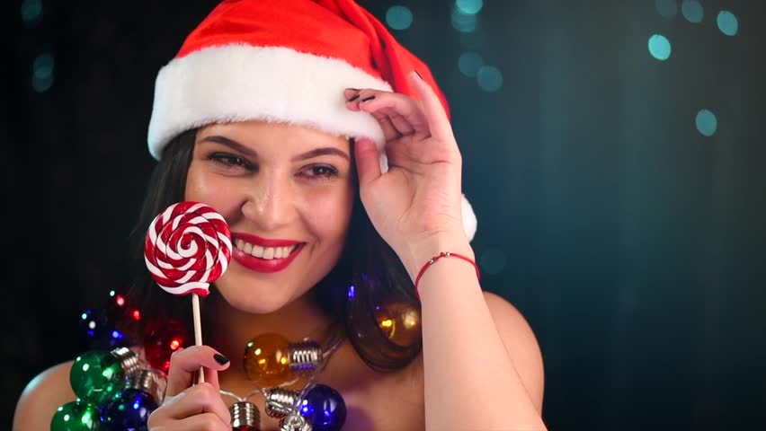 Christmas Woman in Santa hat laughing, dancing and celebrating, New Year party. Beautiful joyful smiling girl with Christmas Lollipop candy and garlands over dark background. Slow motion 4K UHD video | Shutterstock HD Video #1020791254