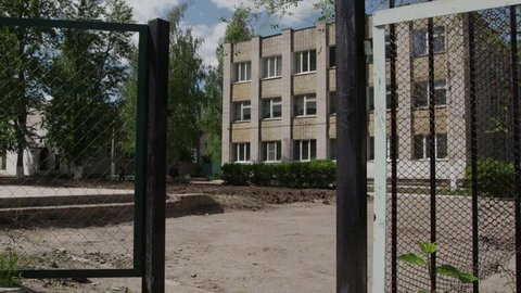 White brick school building with black fence