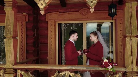 Groom and bride drink coffee on a balcony of wooden log chalet cottage in village while drone camera flies away revealing mountains and forest covered with snow. Winter wedding honeymoon inspiration.