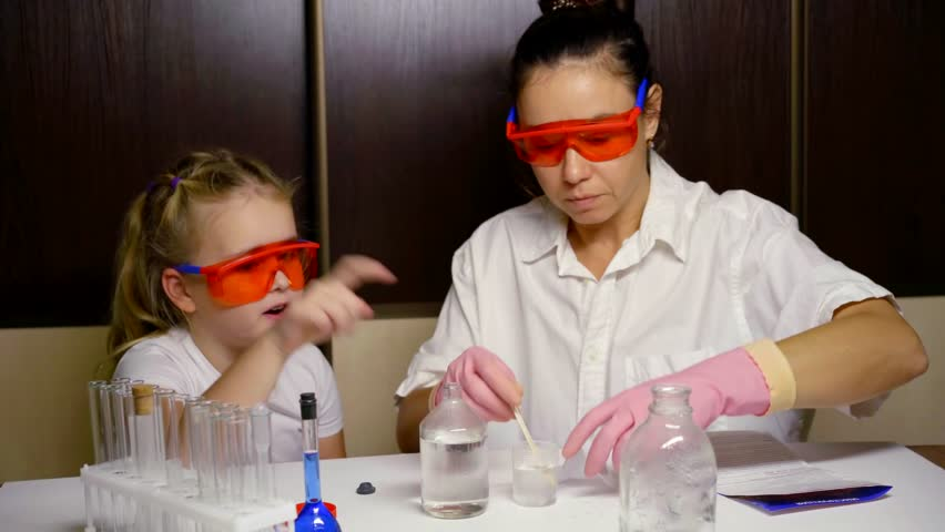 Woman is reading instruction for chemical set and little girl is helping, perform experiment | Shutterstock HD Video #1020857674