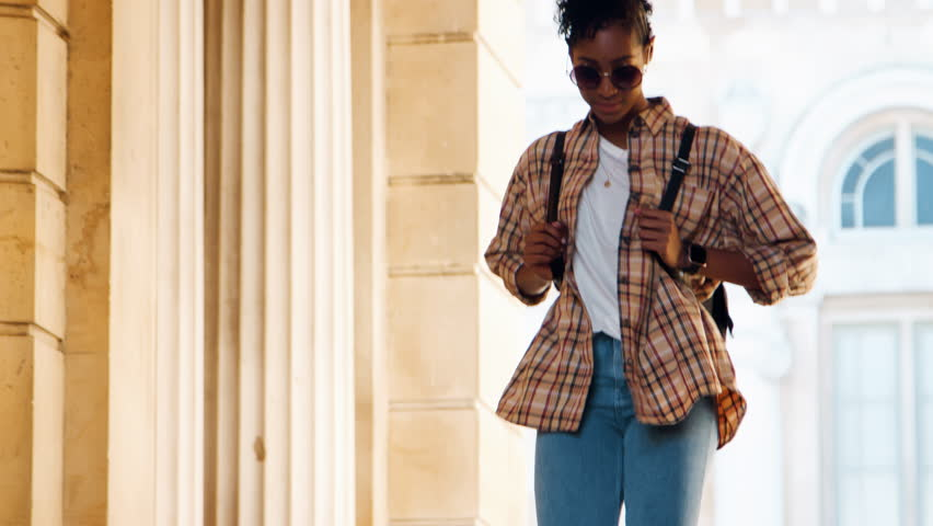 Close up of a fashionable young black woman wearing sunglasses and a plaid shirt walking down stairs outside a historical building, selective focus   Shutterstock HD Video #1020861064