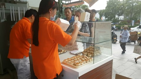 SUZHOU, CHINA - SEPTEMBER 2018: People queue at popular bakery selling special mooncakes during Mid-Autumn festival in Suzhou, China