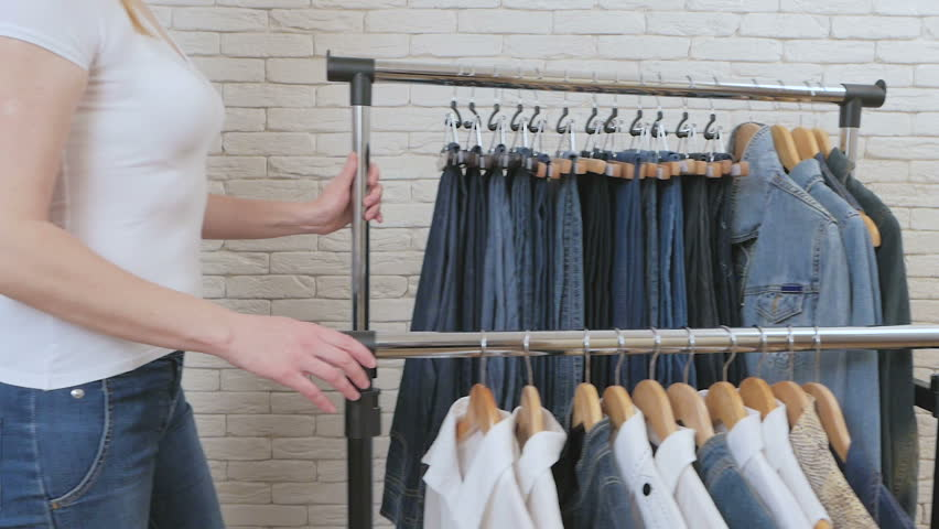 Woman moves shelving with clothes in the store   Shutterstock HD Video #1020896164