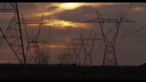 Transmission Tower / Power Tower in the Desert at Sunset with Cloudy Skies from Dusk to Darkness