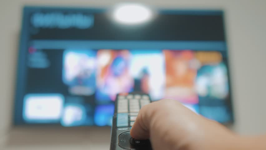 Smart tv with apps and hand. Male hand holding the remote control turn off smart tv . man hand controls TV holding remote. TV concept internet lifestyle online cinema | Shutterstock HD Video #1020911104