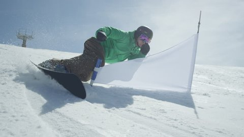 SLOW MOTION: Race snowboarder riding slalom between the gates