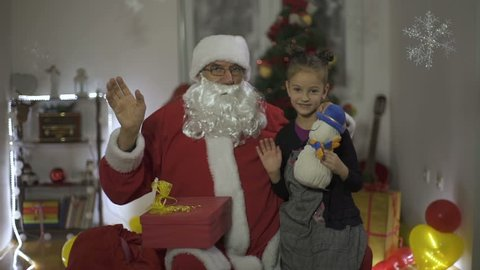 Little girl sitting with Santa Claus, holding gift snowman doll and waving hand like best wishes, decorated Christmas tree and box with presents, concept happy new year or merry Christmas, slow motion