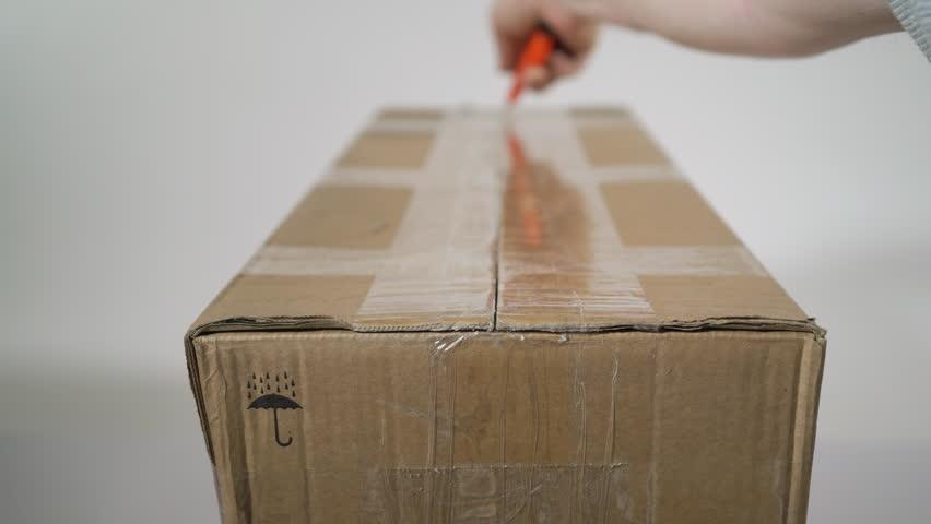 Man opening parcel cardboard box | Shutterstock HD Video #1020985354