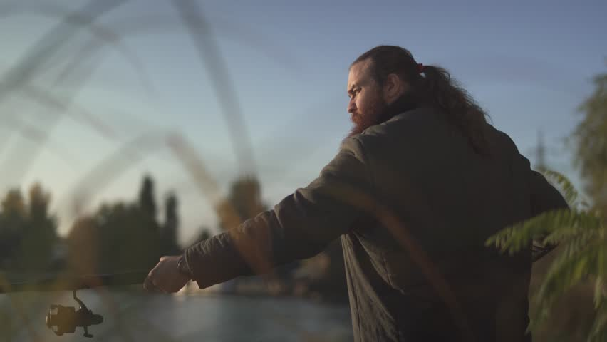 Bearded fisherman fishing on the river. Fisher stands on the river bank with the rod. | Shutterstock HD Video #1020996664
