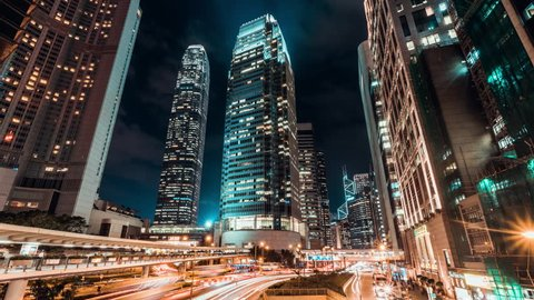 4K UHD Time-lapse cityscape at night of Hong Kong city business district with traffic light trails and office buildings, zoom out effect