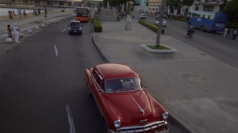HAVANA, CUBA - Oct 18, 2018: Establishing drone aerial shot of classic 1950's American Vintage Taxi Car driving on street. La Habana Vieja Old Havana is iconic popular tourist destination travel.