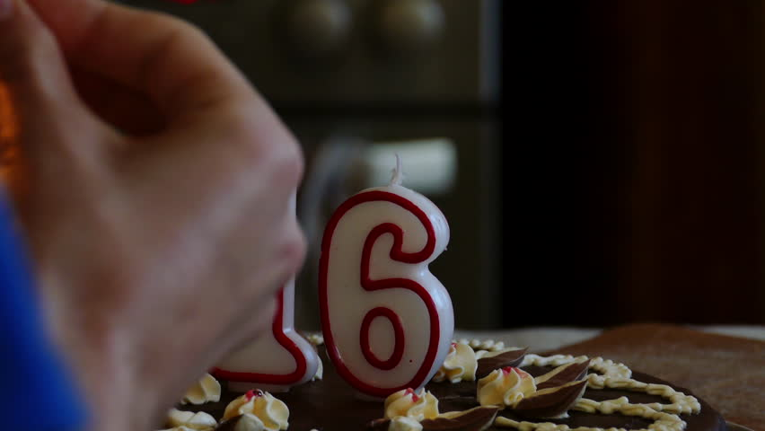 Hand lighting a Sixteenth Birthday cake with numerical candles