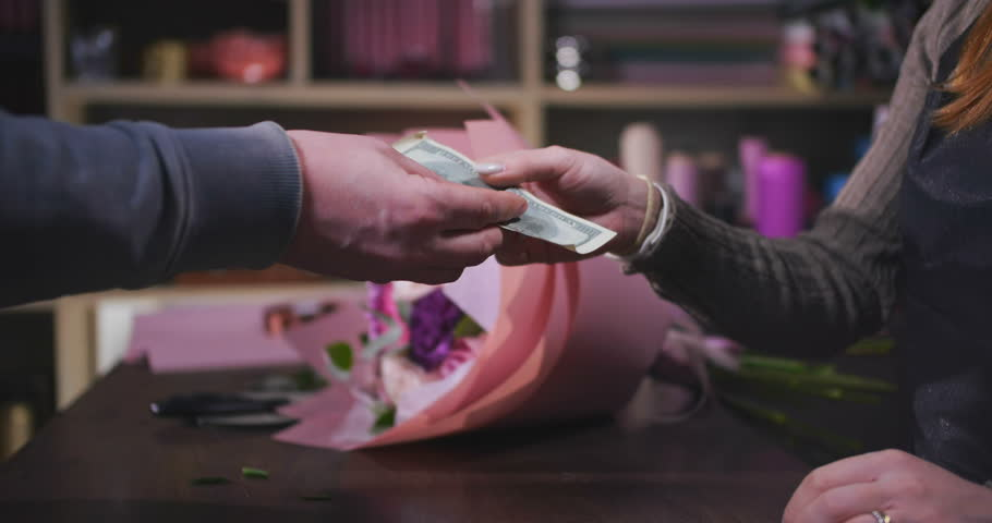 Man buying flowers paying by cash. Florist giving a bouquet to the customer. Small business concept | Shutterstock HD Video #1021092664
