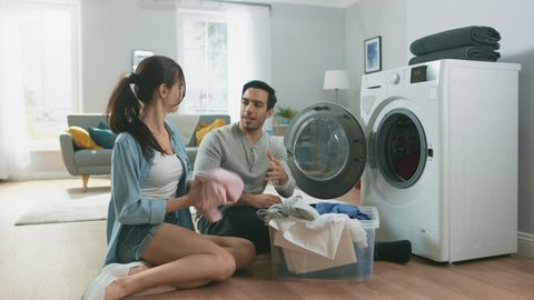 Beautiful Young Couple Sit Next to a Washing Machine at Home. They Talk, Laugh and Load the Washer with Dirty Laundry. Bright and Spacious Living Room with Modern Interior.