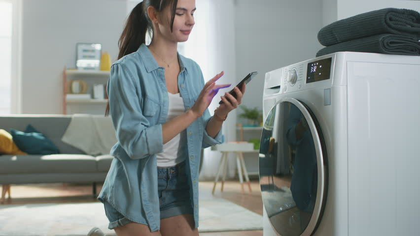 Beautiful Young Woman Sits on Her Knees Next to the Washing Machine. She Loaded the Washer with Dirty Laundry and Configured the Wash With Her Smartphone. Shot in Living Room with Modern Interior.