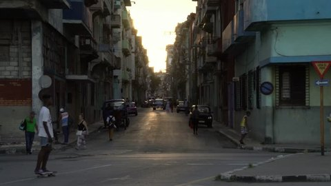 HAVANA, CUBA - Oct 18, 2018: golden hour sun, classic American 1950's Vintage cars drive on old alley street. La Habana Vieja is iconic popular tourist destination travel.