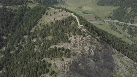 Aerial footage of Rock Del Quer at the green Pyrenean mountains in the summer. Drone flies over the Rock Del Quer, between green mountains of Andorra La Vella, Andorra. There are winding roads in the