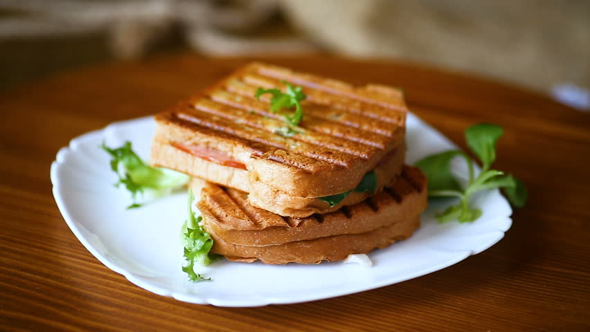 Hot double sandwich with lettuce leaves and stuffed in a plate | Shutterstock HD Video #1021173844