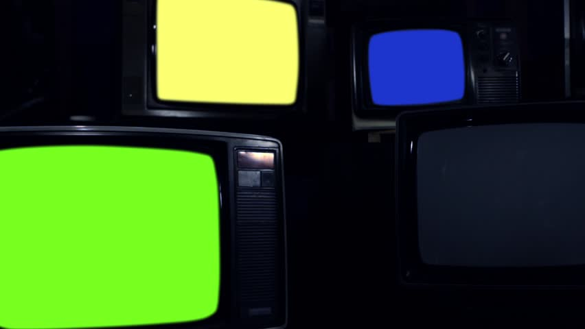 "Old Tvs Turning On Different Chroma Screen. Dark Tone. Zoom In. Ready to Replace Chroma Screens with any Footage or Picture you Want. You can do it with ""Keying"" (Chroma Key) effect. 
