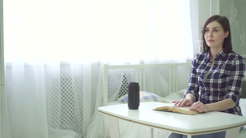 a blind, visually impaired beautiful young woman reads a book, uses a voice assistant, has a question