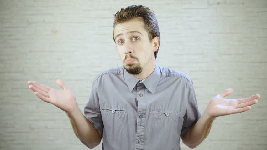 Man shrugs shoulders with funny expression in slow motion HD. Medium static shot of young man in focus looking at the camera doesn't know and makes shrugging expression with hands. | Shutterstock HD Video #1021295584