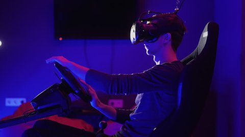 Young man using virtual reality headset and playing in car drive simulator in dark blue room. Video game concept. Closeup shot