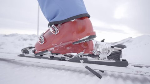slow motion stepping in ski binding close up, man starting skiing on slope in winter, shallow focus