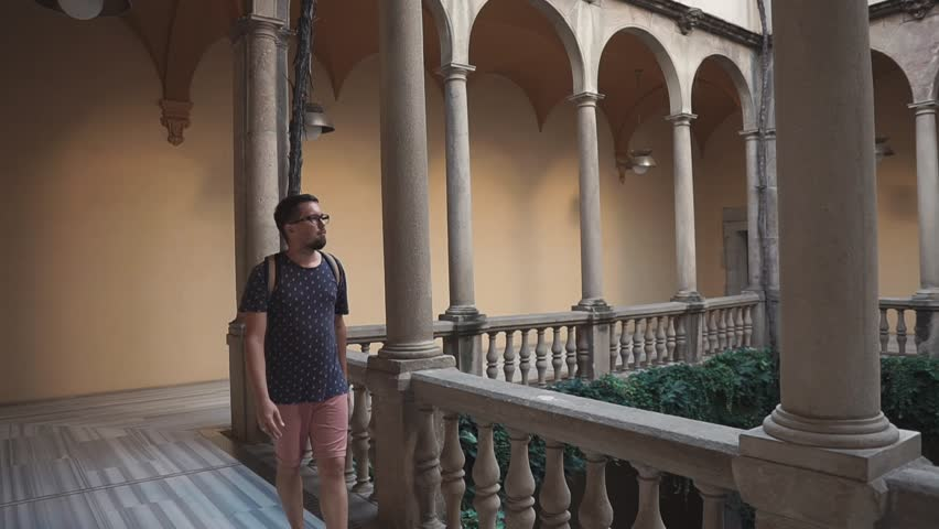 Adult caucasian man with backpack wearing glasses walking around of historic building on summer vacation. Beautiful touristic places. | Shutterstock HD Video #1021321804
