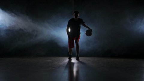 one young adult man, basketball player dribble ball, dark indoors basketball court slow motion