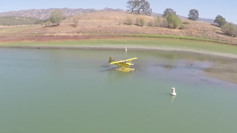 A small floatplane taxiing to shore after landing in a small lake inlet.