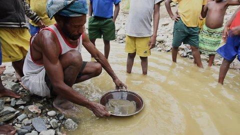 Vanimo, Papua New Guinea - 05 19 2017: Man Sifting Through Dirty Water Puddle In Vanimo Papua New Guinea