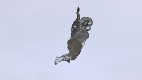 White clear figure of a cupid toy with golden wings playing the lyre, rotating on a light background. Loop