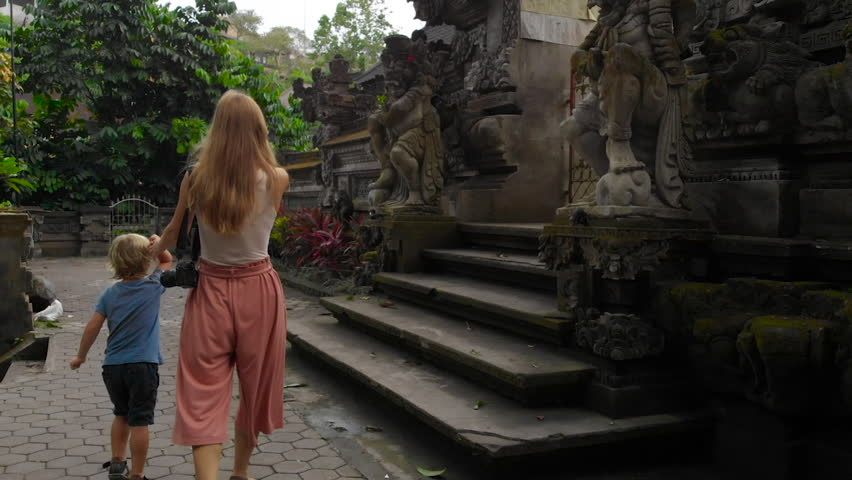 Slowmotion steadicam shot of young woman and hel littl son walking around the Pura Gunung Lebah temple in Ubud on the Bali island | Shutterstock HD Video #1021438684