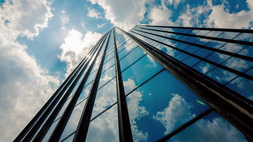 4K 30p Huge,tall glass skyscraper dramatic sun and dark clouds reflection timelapse.Beautiful thick white summer clouds and sun with light rays reflected on the surface of a big corporate building. | Shutterstock HD Video #10214396