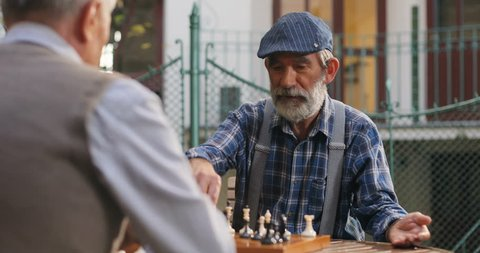 Back view on the senior caucasian man sitting with his old best friend at the chess game and disputing something. Outside. Rear.