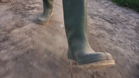 Farmer walking on dusty dirt country road in sunset, close up of rubber boots, low angle view
