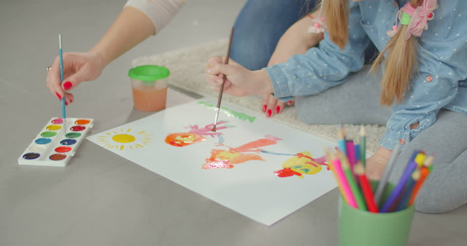 Close-up of hands of caring mother and elementary age daughter painting together on white paper while enjoying leisure at home. Caring mum developing creativity of child through painting. | Shutterstock HD Video #1021482484