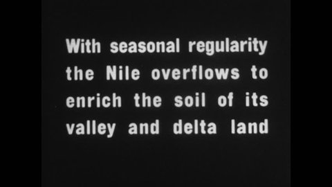 """1930s: Intertitle """"With seasonal regularity the Nile overflows to enrich the soil of its valley and delta land"""". Two Felucca sailboats move on the Nile. Two men ride camels in the water."""