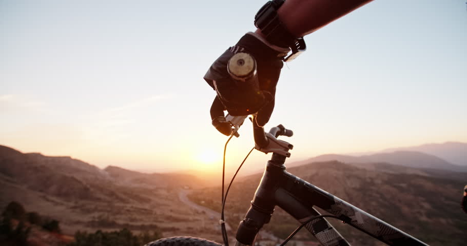 Mountain biker putting his hands on bicycle wheel, ready to go down the mountain in sunset - gettng away from it all, activity, extreme  #1021585624